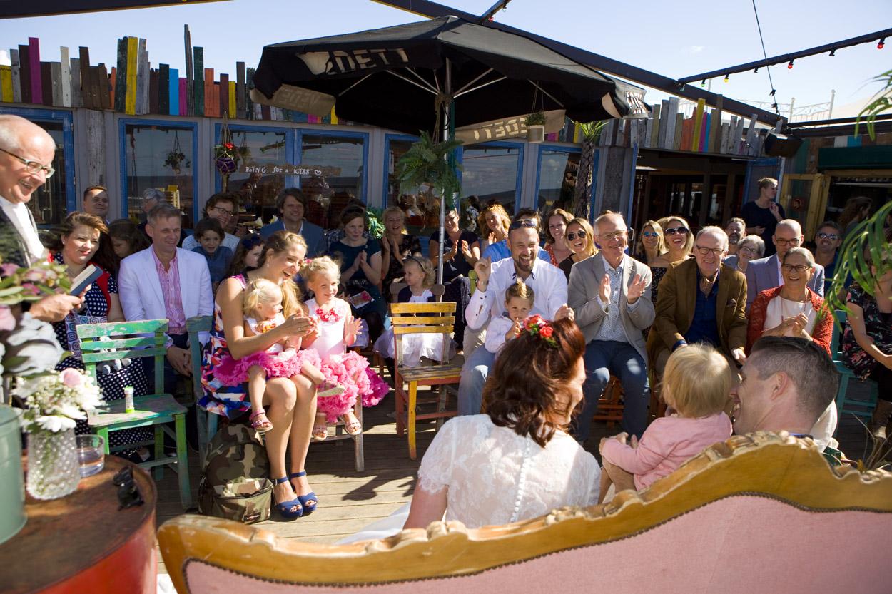Spontane bruidsfotografie bruiloft ceremonie gasten strandbruiloft trouwreportage Beachclub Indigo Scheveningen