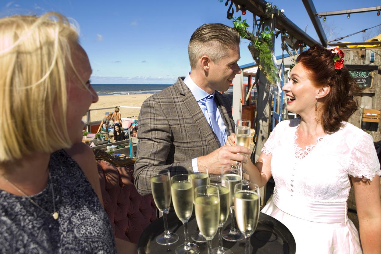 Spontane bruidsfotografie bruiloft proostmoment proosten bubbels bruidspaar strandbruiloft trouwreportage Beachclub Indigo Scheveningen
