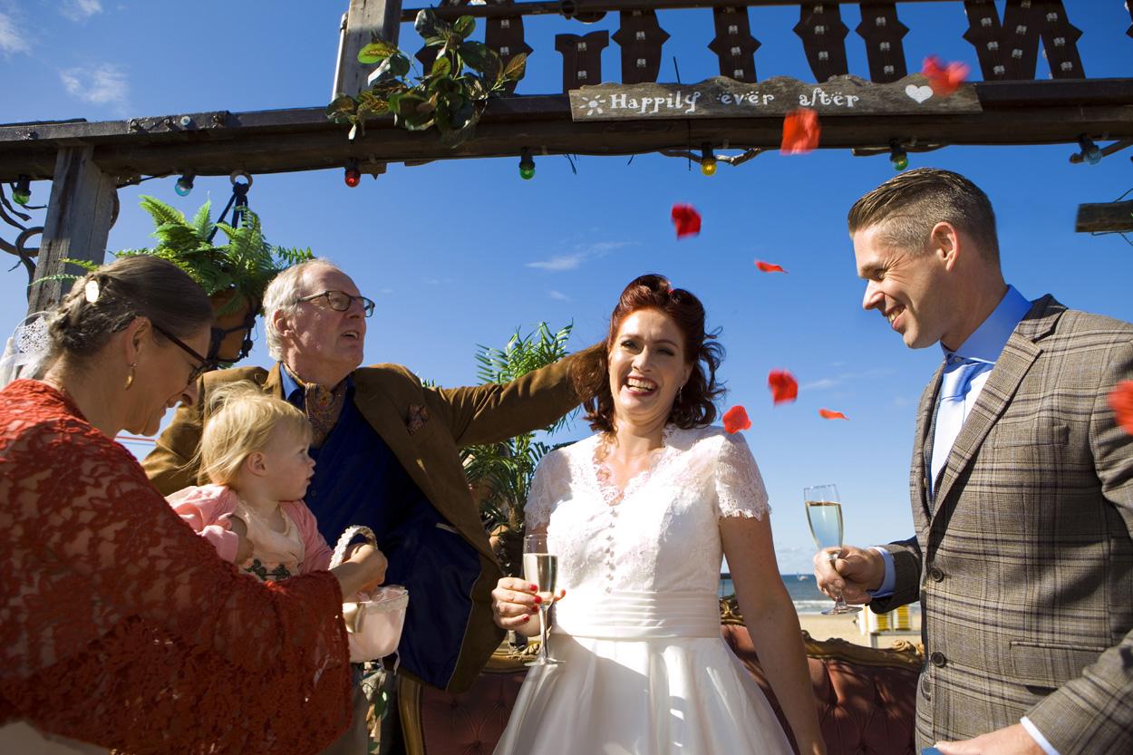 Spontane bruidsfotografie bruiloft rozenblaadjes gooien strandbruiloft trouwreportage Beachclub Indigo Scheveningen