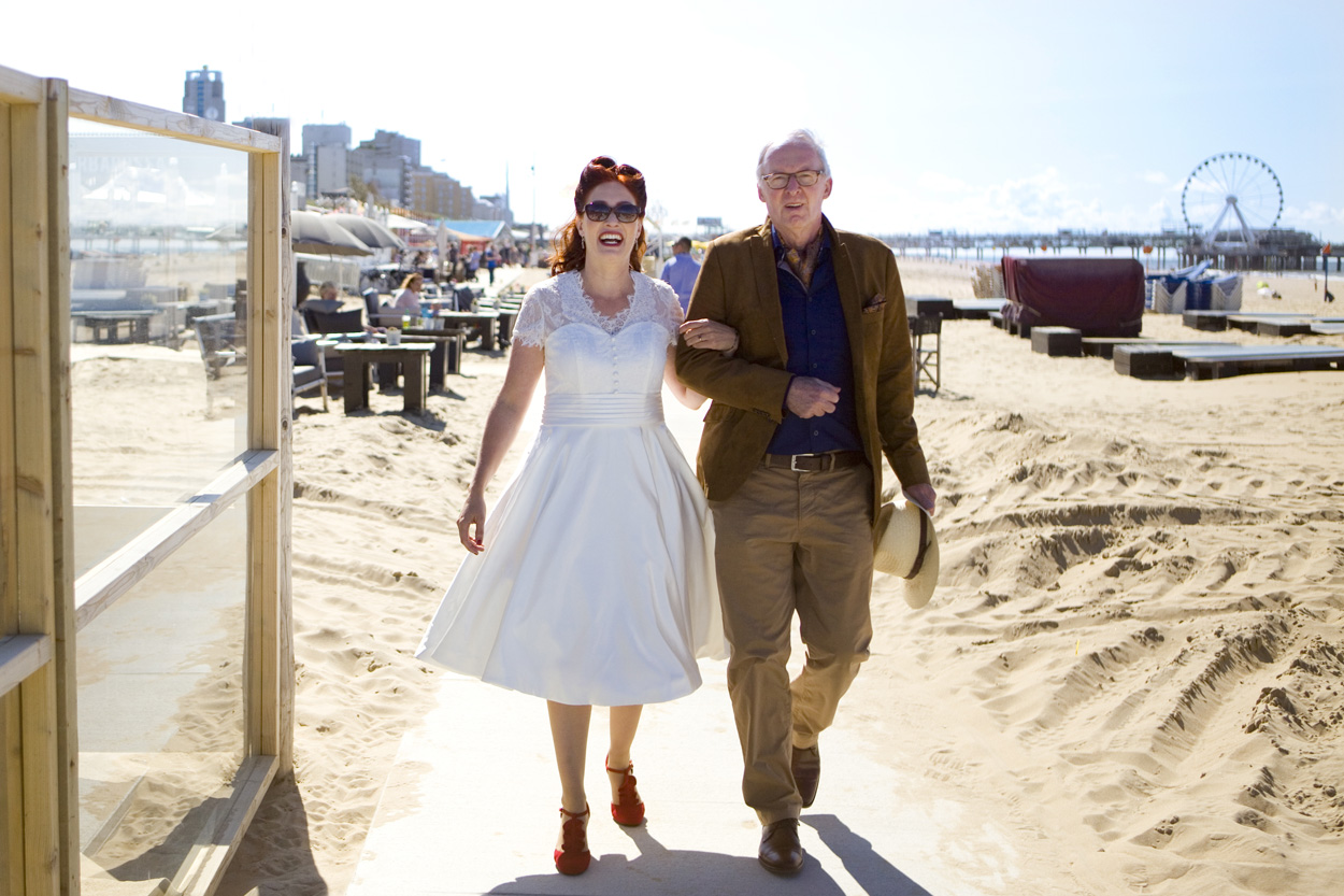 Spontane bruidsfotografie bruid met vader weggeven strandbruiloft trouwreportage Beachclub Indigo Scheveningen