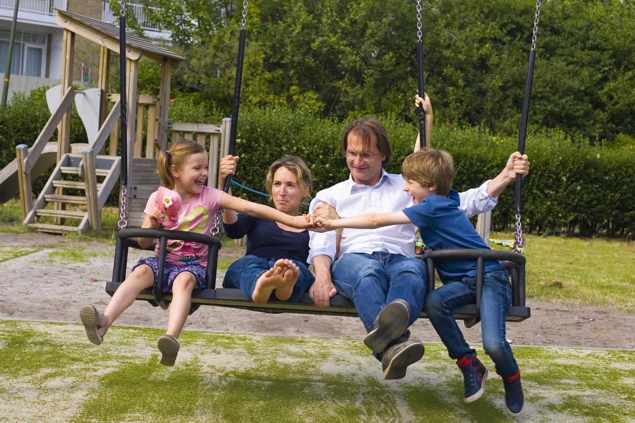 Foto gezinsportret familieportret in speeltuin schommel Den Haag