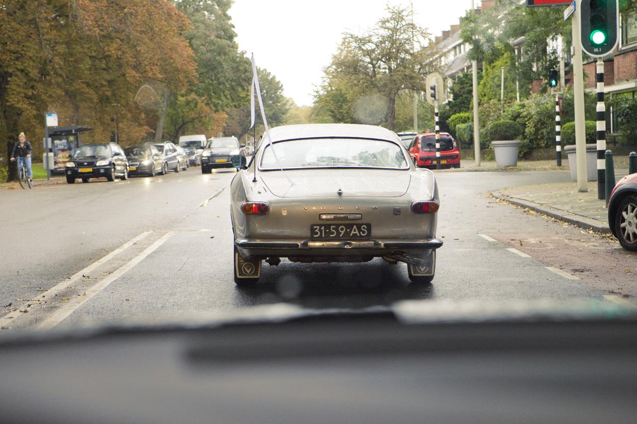 onderweg in de trouwauto Volvo p1800  bruiloft Kasteel De Wittenburg Wassenaar  bruiloft trouwauto Volvo P1800 S Coupé