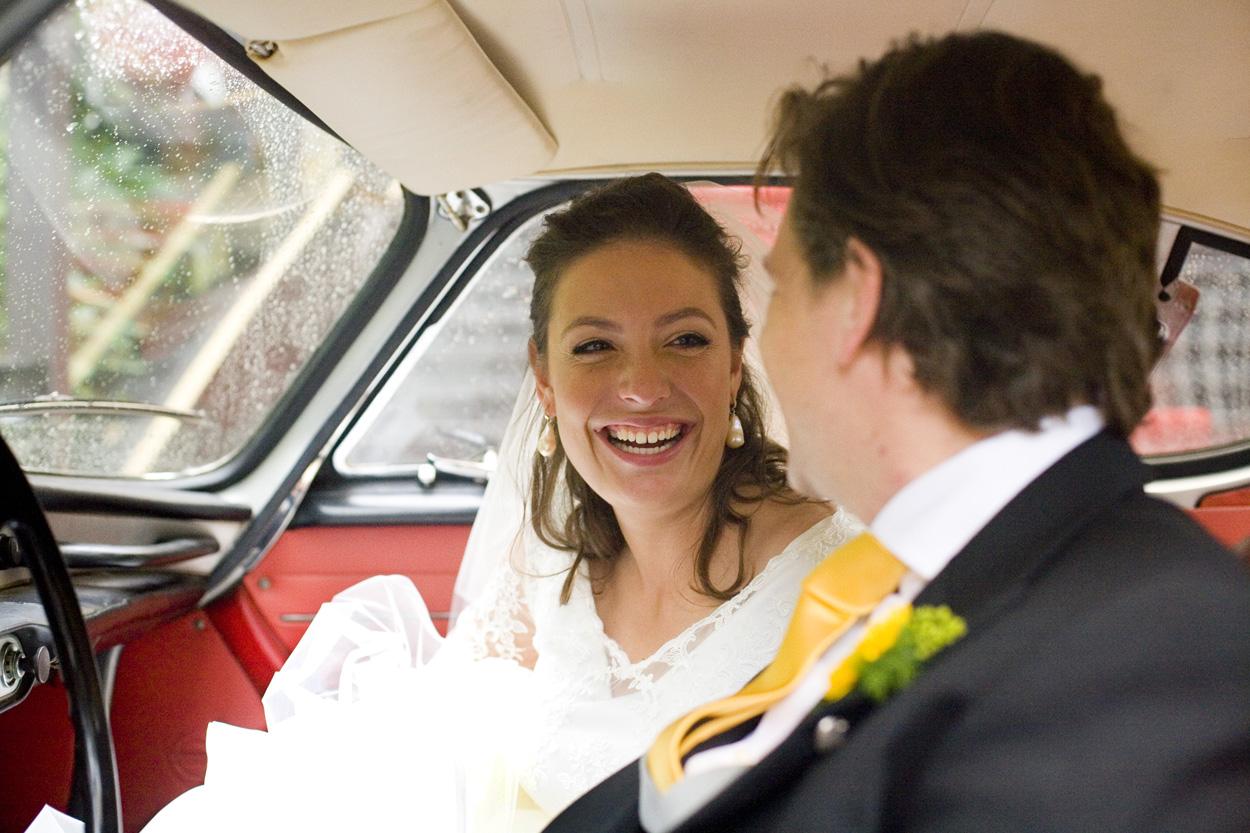 lachende bruid in trouwauto bruiloft Kasteel De Wittenburg Wassenaar  bruiloft bruidspaar in auto Volvo P1800
