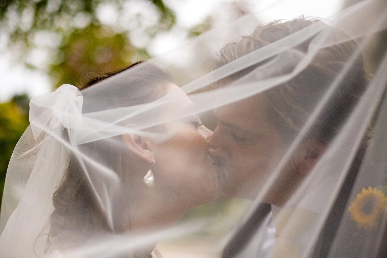 kus bruidspaar onder sluier bruiloft Kasteel De Wittenburg Wassenaar  bruiloft trouwreportage rode loper kus bruidspaar sluier