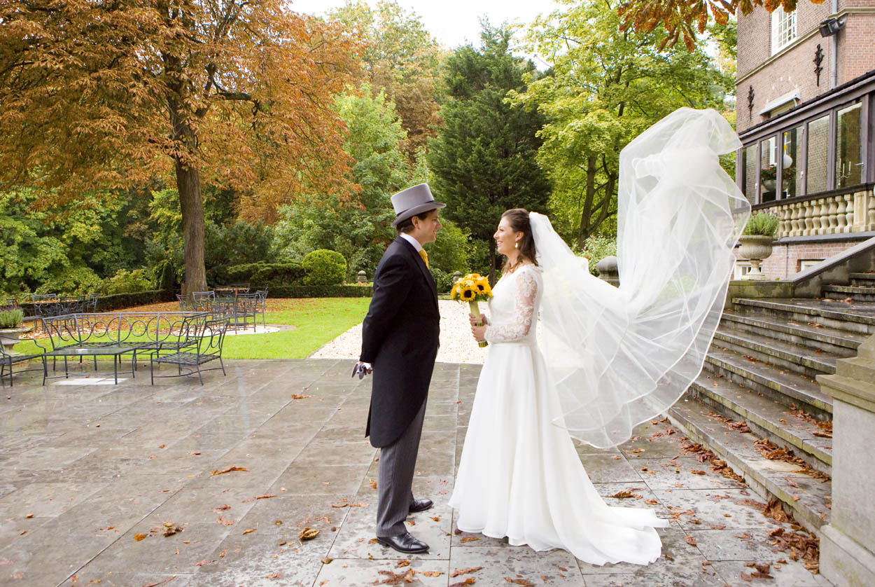 bruidspaar op bruiloft Kasteel De Wittenburg Wassenaar sluier van trouwjurk in de wind  in de herfst