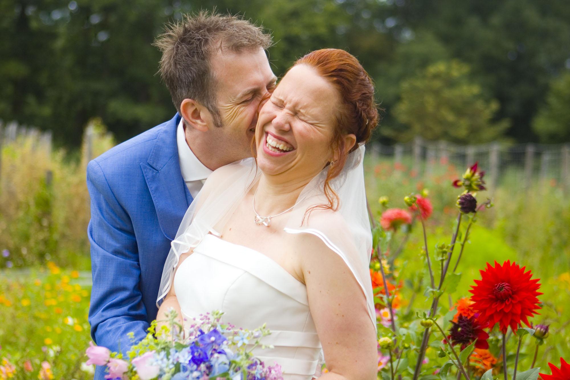 Bruidsfpaar in bloemen tuin bruiloft De Hertenhorst Delft trouwreportage moestuin Delftse Hout