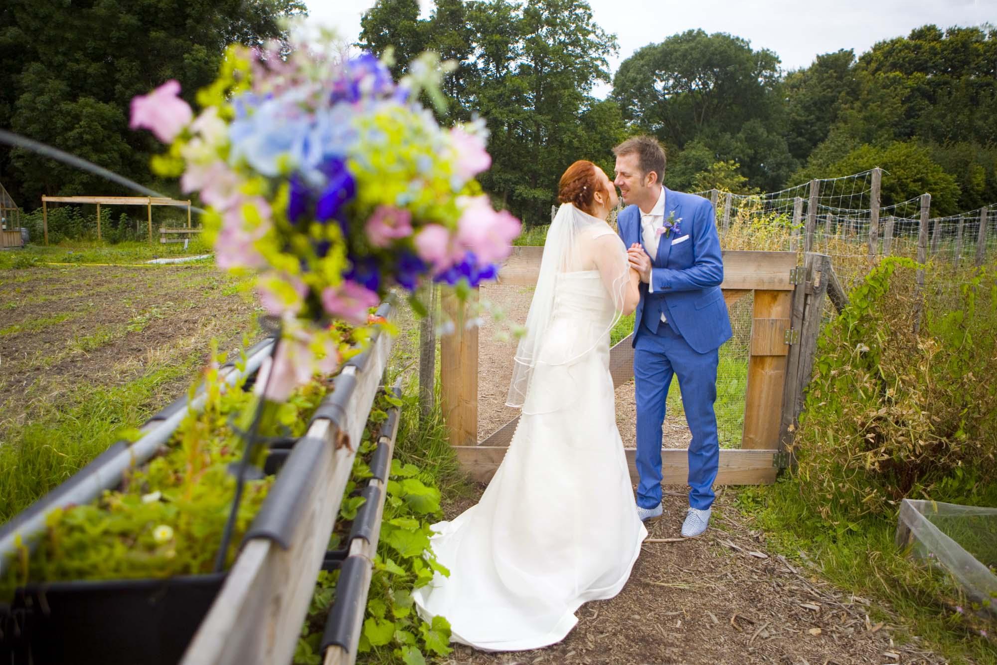 kus bruidspaar in tuin bruiloft De Hertenhorst Delft trouwreportage moestuin Delftse Hout