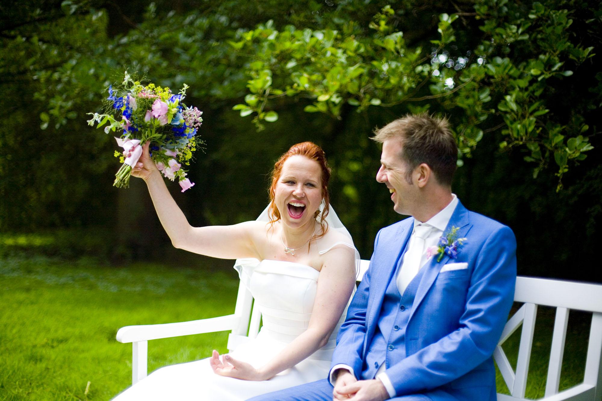 Bruid lach met trouwboeket bruiloft De Hertenhorst Delft bruid ceremonie buiten
