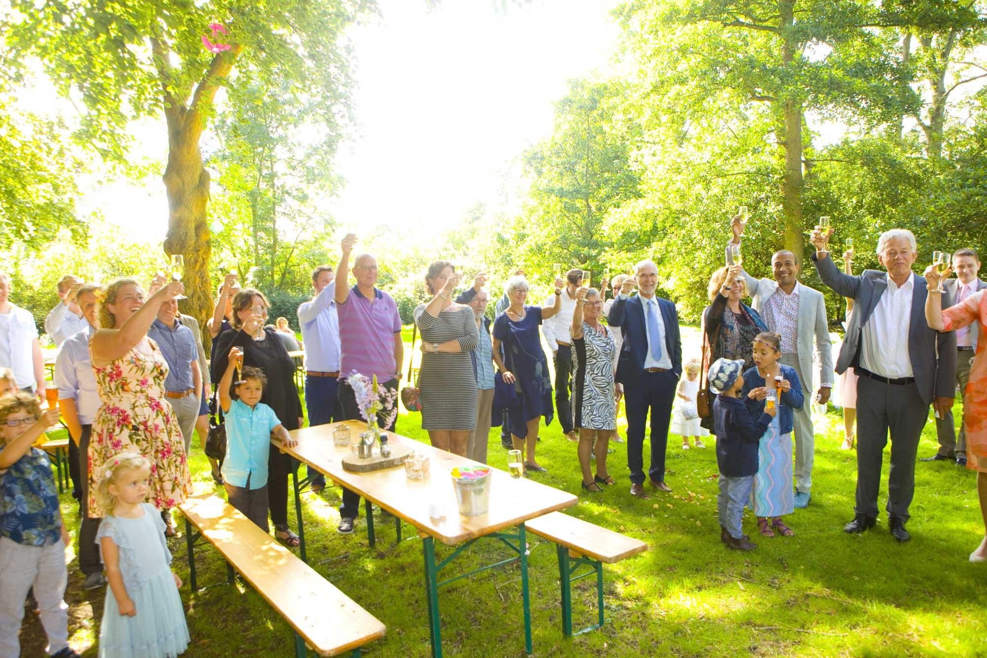 Bruidsfotografie bruiloft zomerbruiloft proosten gasten tijdens borrel buiten Hertenhorst Delft