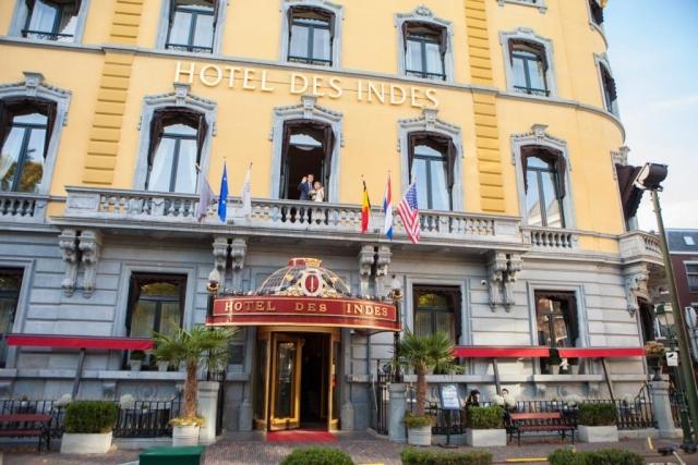 Bruidspaar zwaaien op balkon balkonscene in Hotel Des Indes Den Haag