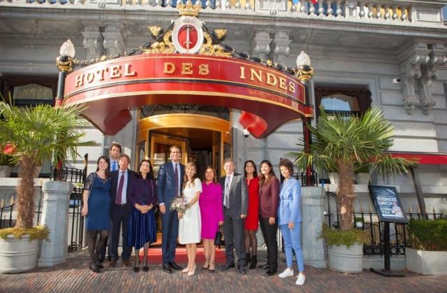 groepsfoto met bruidspaar voor entree Hotel Des Indes in Den Haag